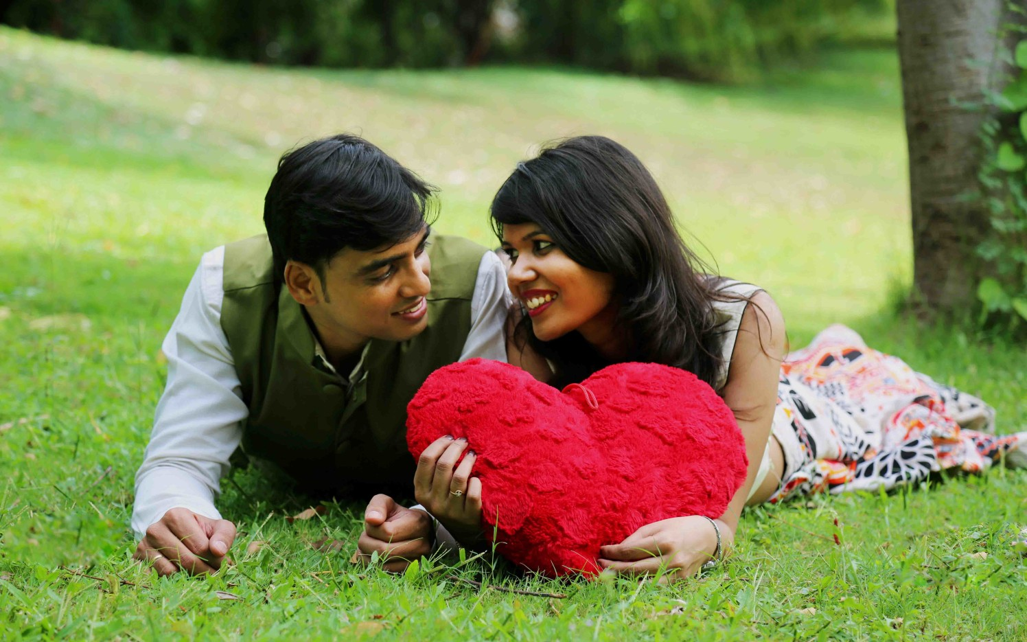 Bride and Groom To-Be Pose With a Heart Shaped Pillow Against a Picturesque Garden Background by Rushil Jadhav Wedding-photography | Weddings Photos & Ideas