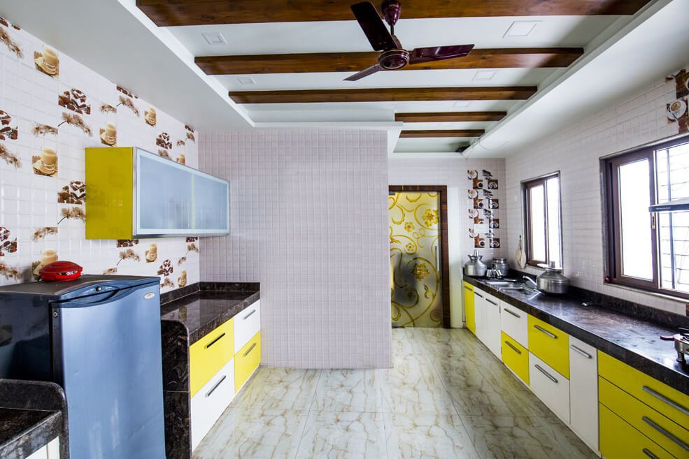Spacious Modular Kitchen with Yellow and White Cabinets and Black Counter Top by Trupti Ladda Modular-kitchen Modern | Interior Design Photos & Ideas