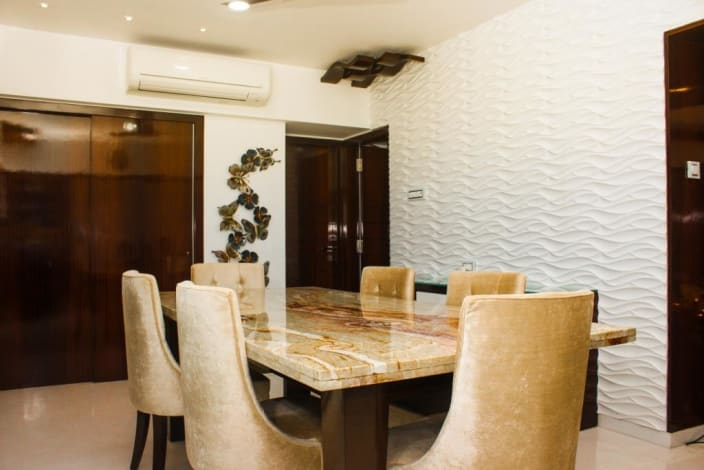 Textured White Wall And Polished Marble Dining Table In Modern Dining Room By Versatile Interiors