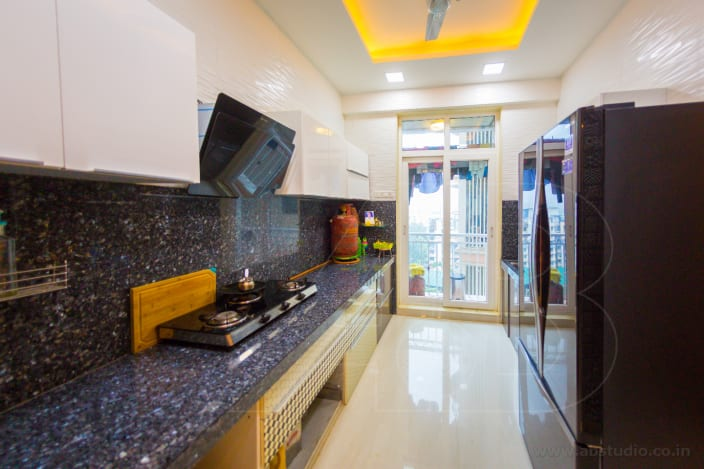 Granite Top Parallel Kitchen With False Ceiling And Cabinets And Sunlight Yellow Led Ceiling