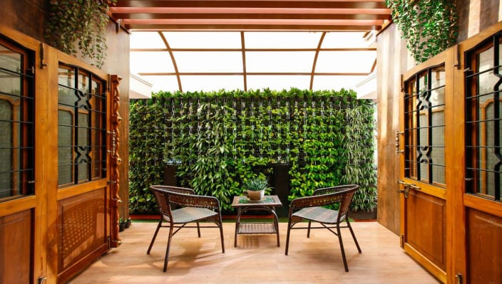 outside space with wall garden and glass top table with chairs