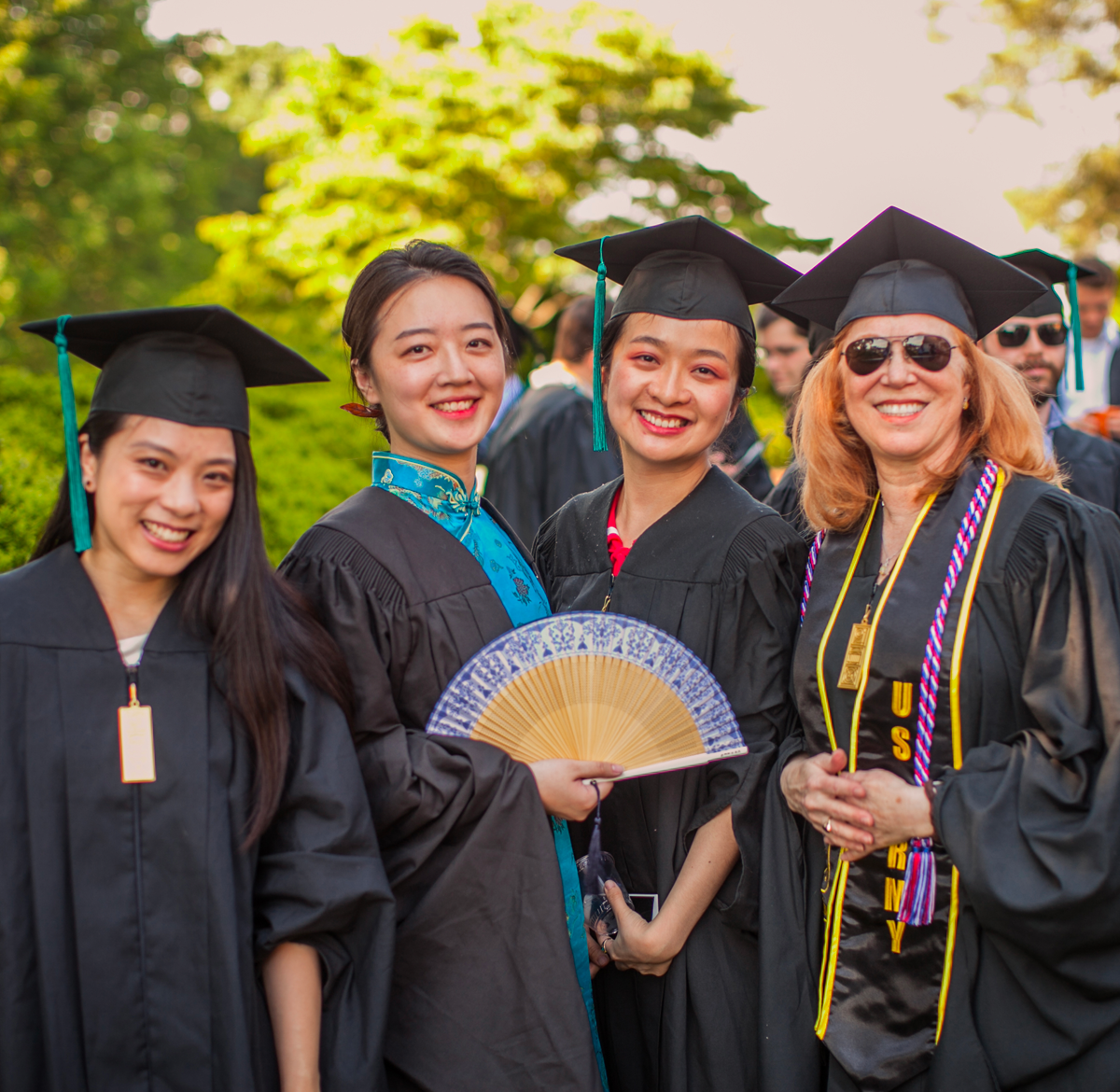 Four women dressed for graduation, one holding a fan