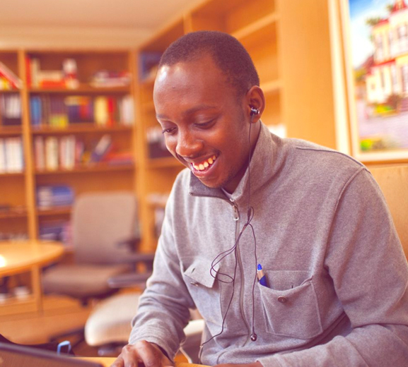 Male student smiling and working on a laptop