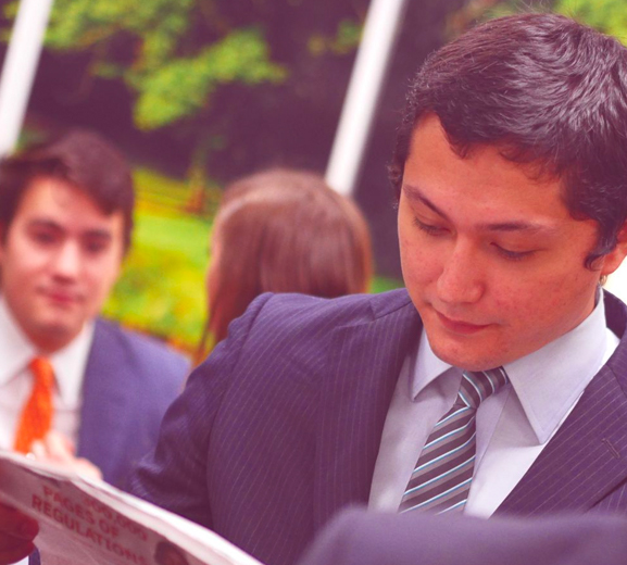 Man in suit looking at a book