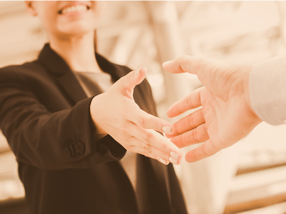 Woman shaking hands with someone out of the photo