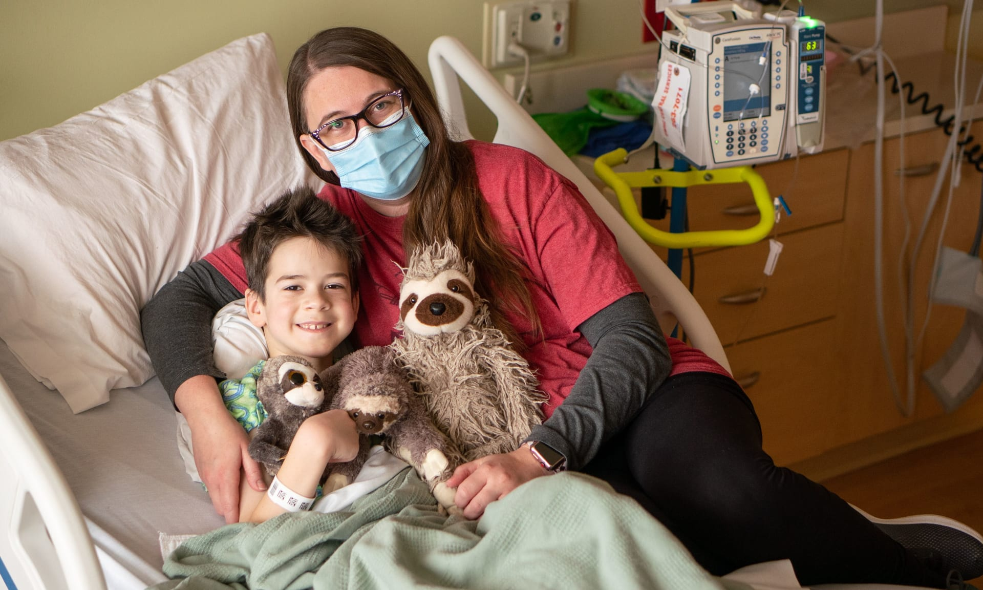 Woman and child in hospital bed with stuffed animals