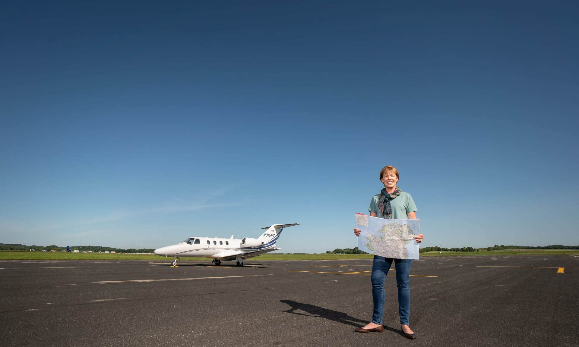 Woman standing in front of small jet holding a map.