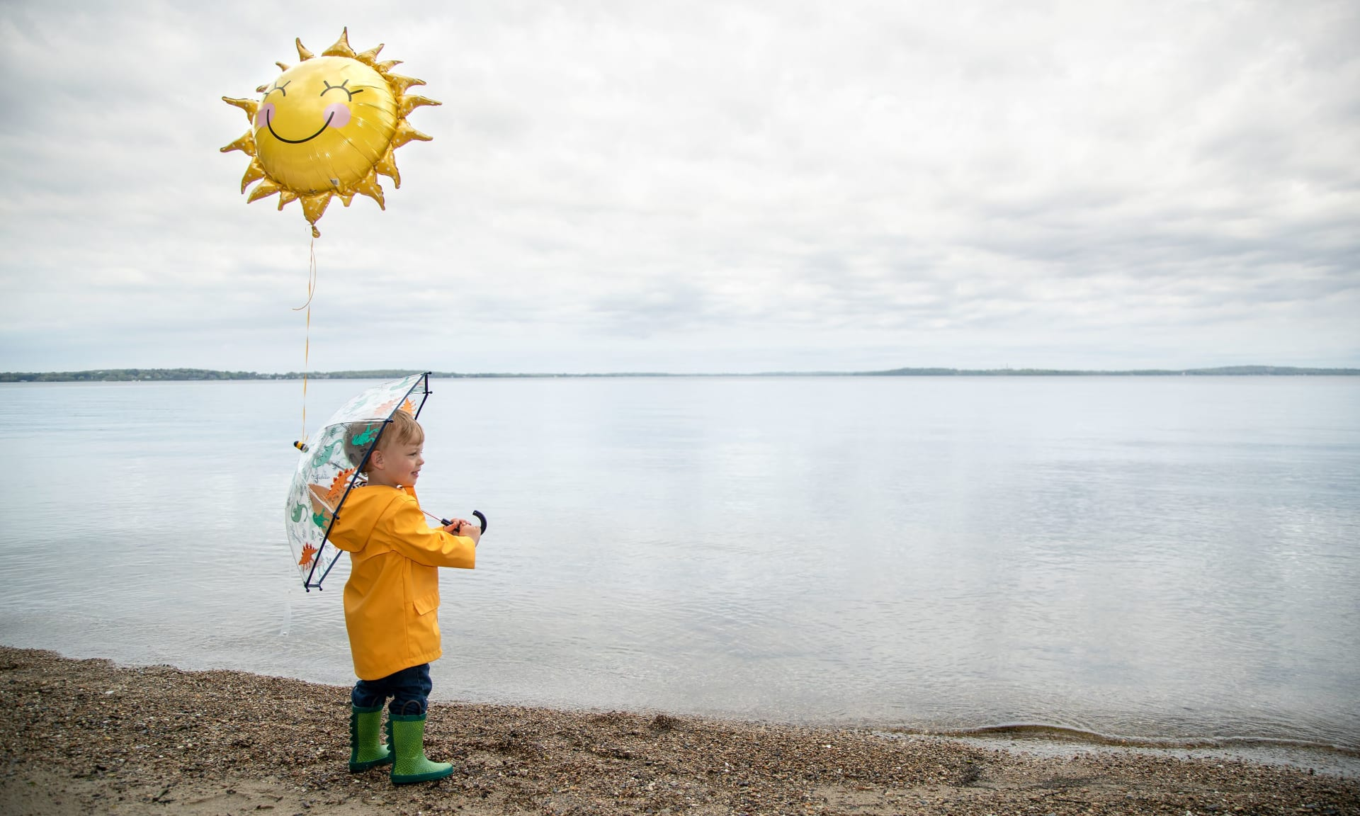 Small boy on the shore of a lake, dressed in a raincoat and holding a balloon.