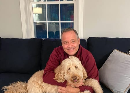 Joe Murray sitting on the couch with his dog, Buddy.
