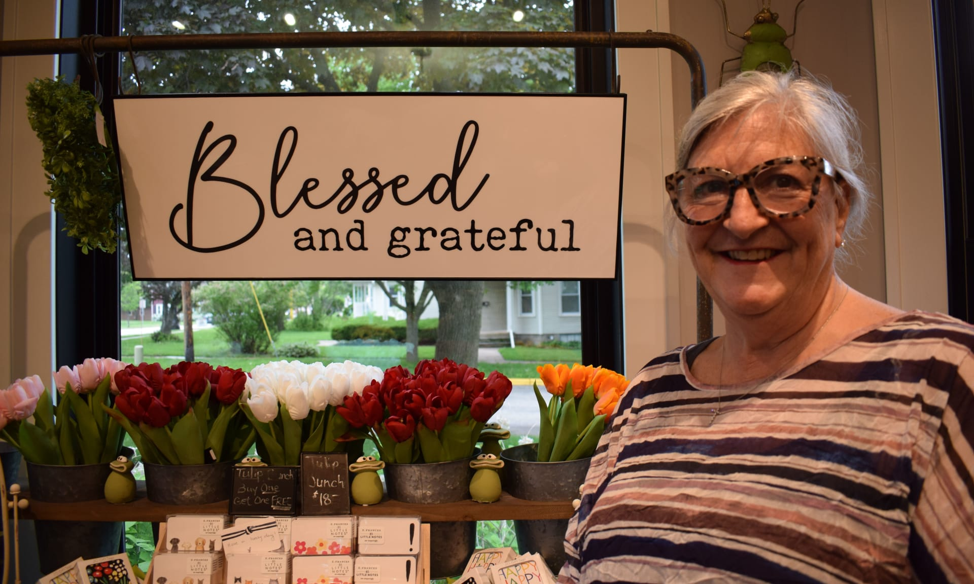 Woman smiling next to sign reading Blessed and grateful