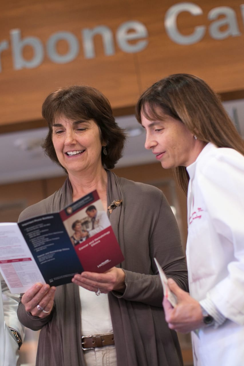 Patient and doctors reading a brochure