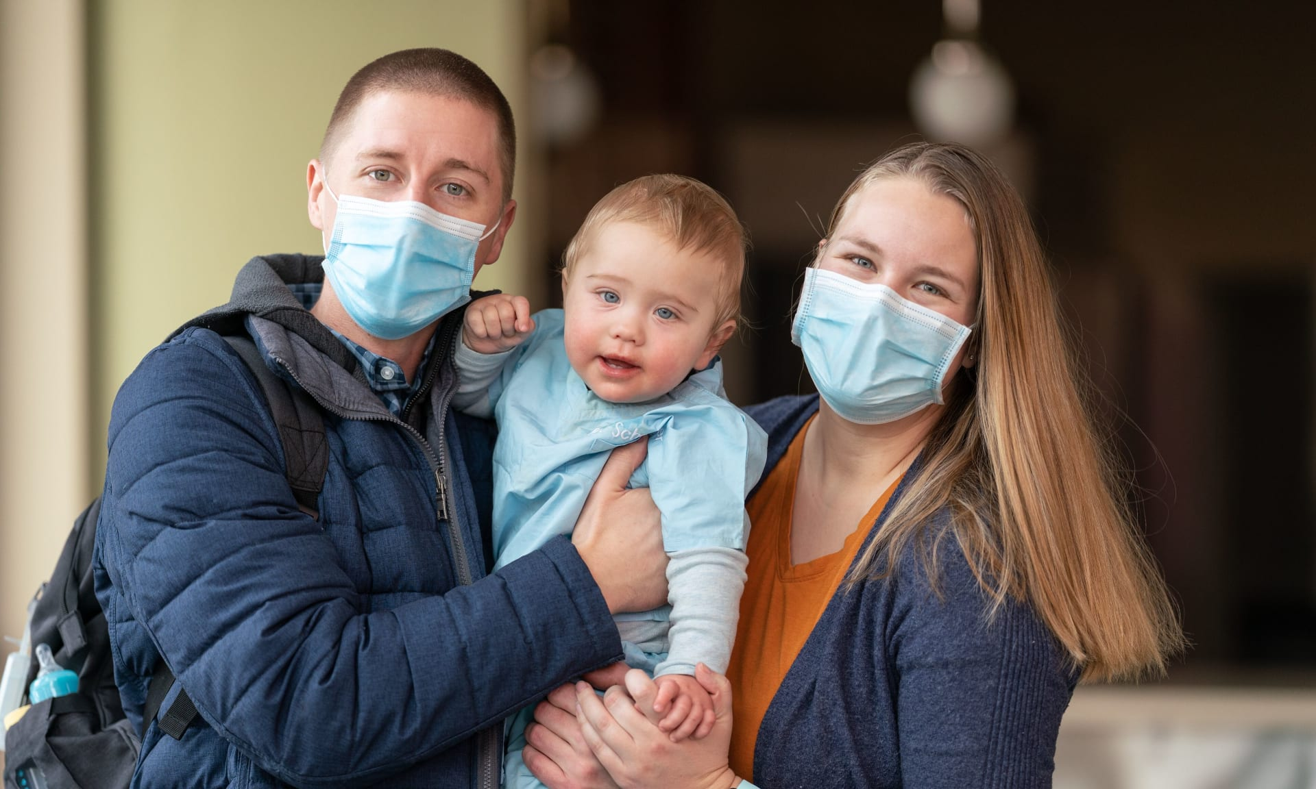 man and woman wearing face masks holding a child