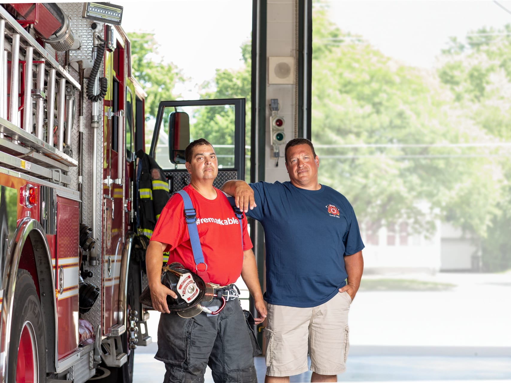 Two firefighters smiling in front of fire engine.
