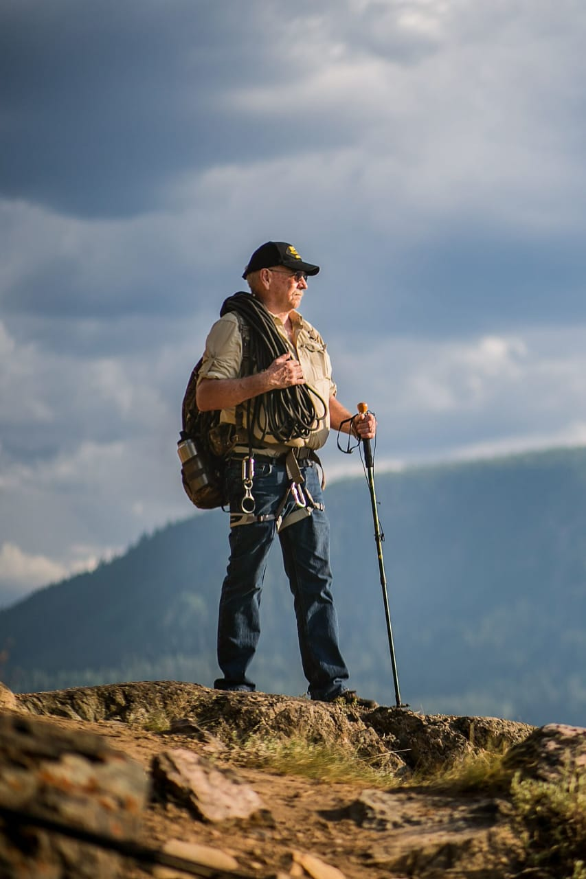 Man in hiking gear standing on top of a mountain peak.