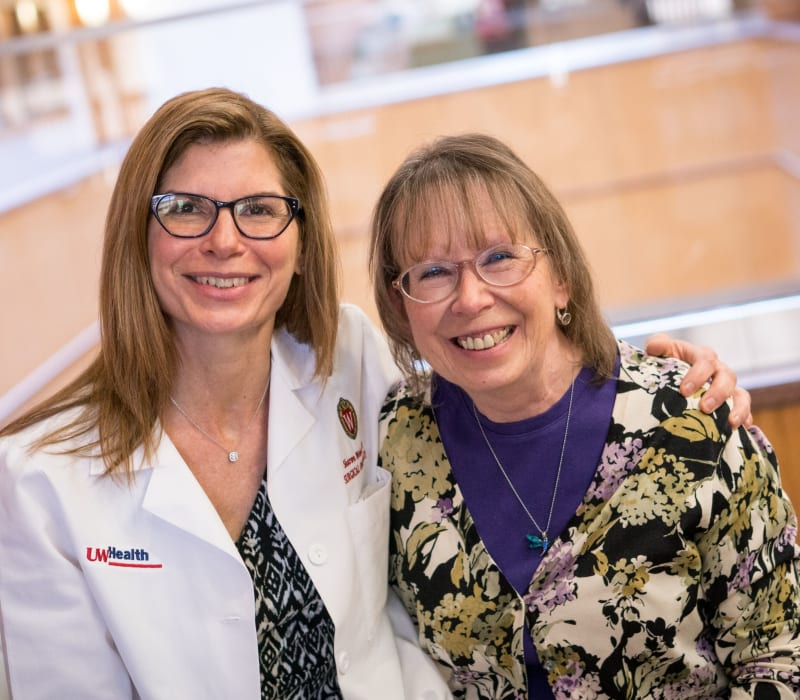 A female doctor and female patient sit together smiling