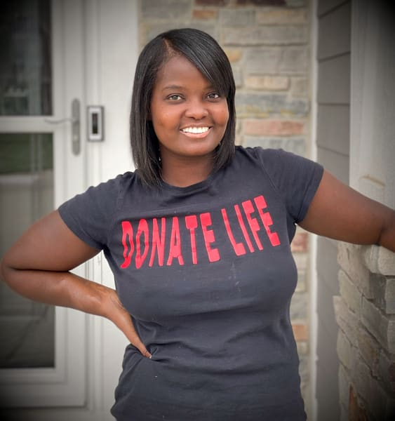 "Woman smiling with ""donate life"" tshirt on."