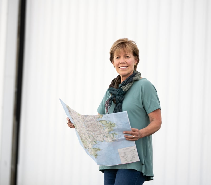 Woman holding map outside airplane hangar.