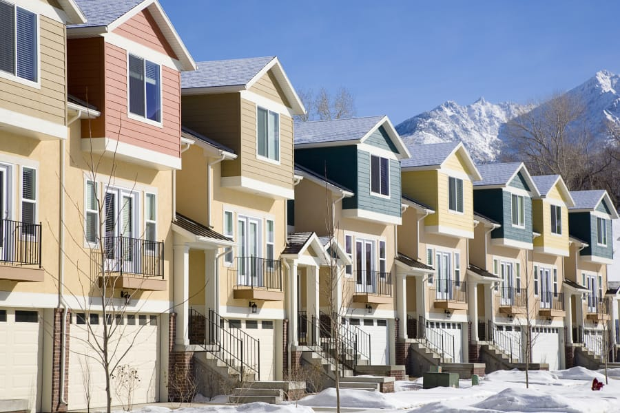 A row of townhouses covered in snow