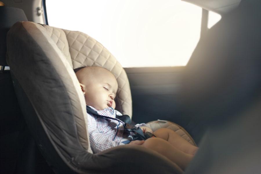 A baby asleep in a rear-facing car seat