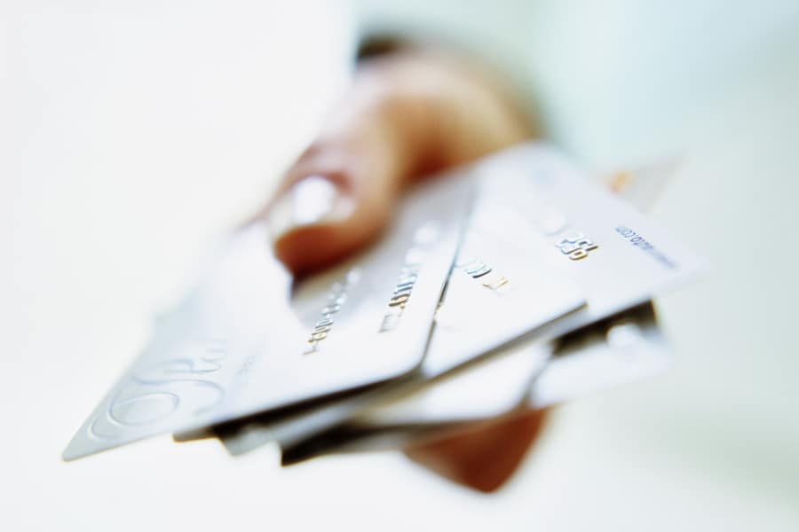 A woman's hand holds a selection of credit cards
