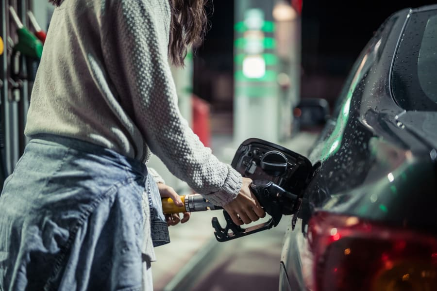 A woman pumps gas into her car