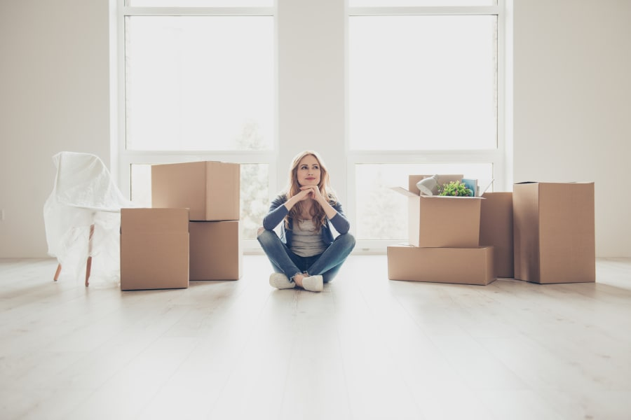 A woman sits in her new home surrounded by boxes