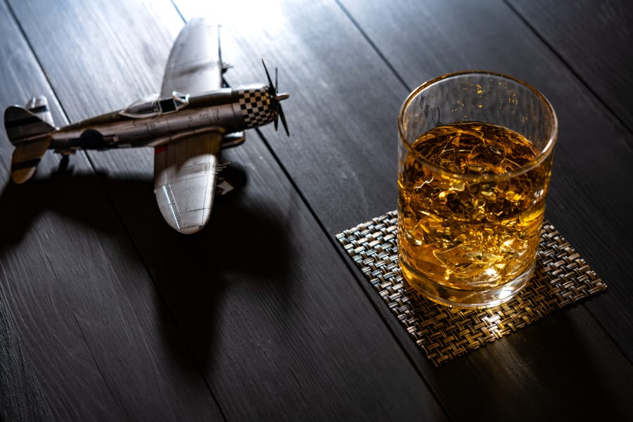A glass of whisky sits next to a toy airplane.