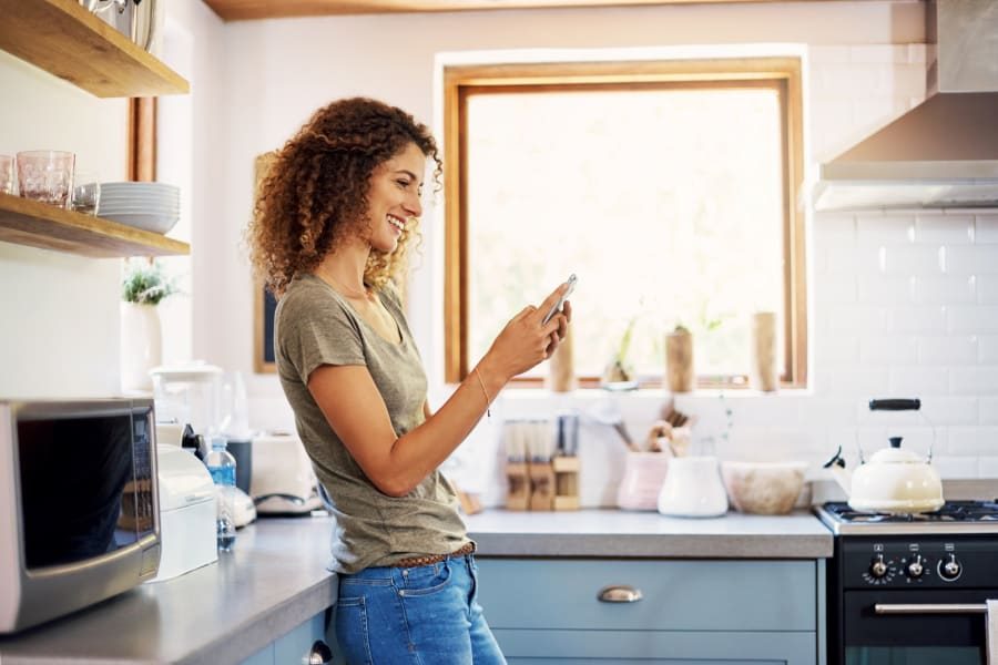 A woman on her phone in the kitchen