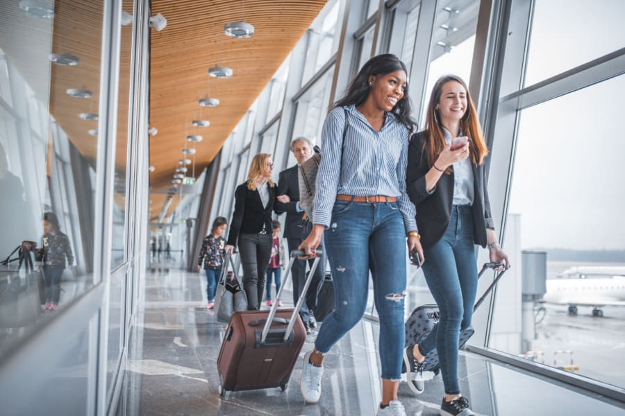 Gen Z travelers roll their suitcases through the airport