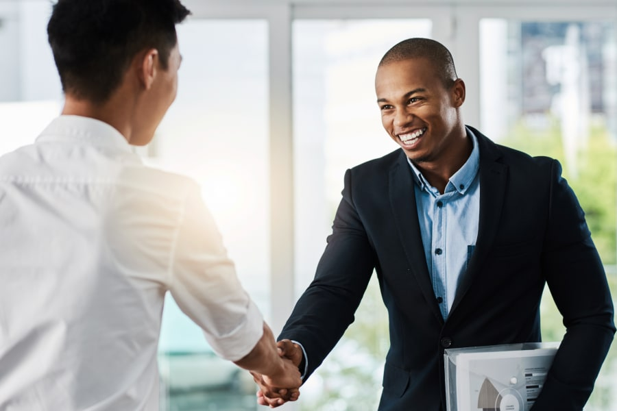 An interviewer and candidate shake hands