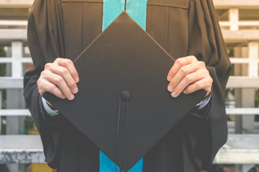 A recent college grad holding their cap