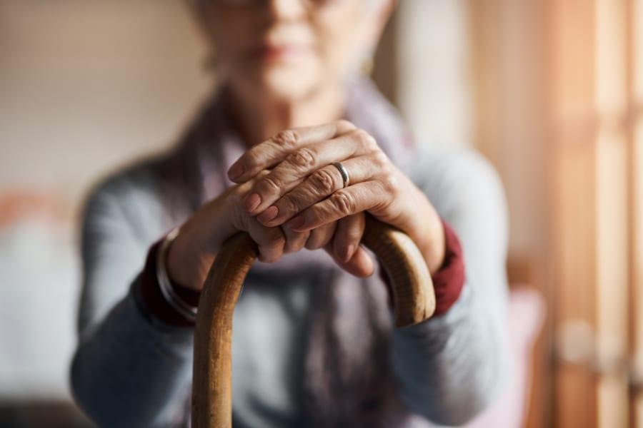 A senior woman holding a cane