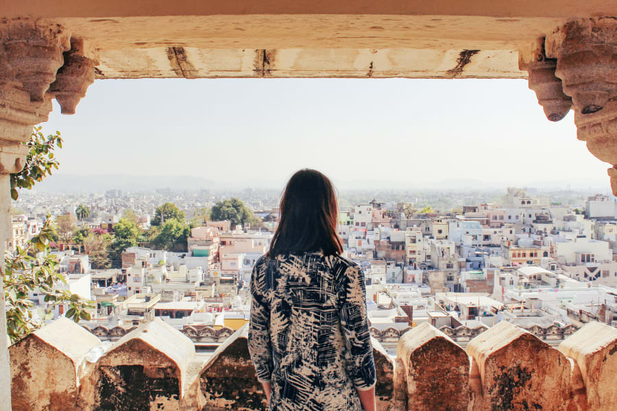 A solo female traveler looks out at a city