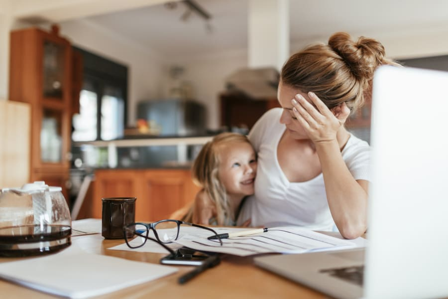 A stressed mother pays bills