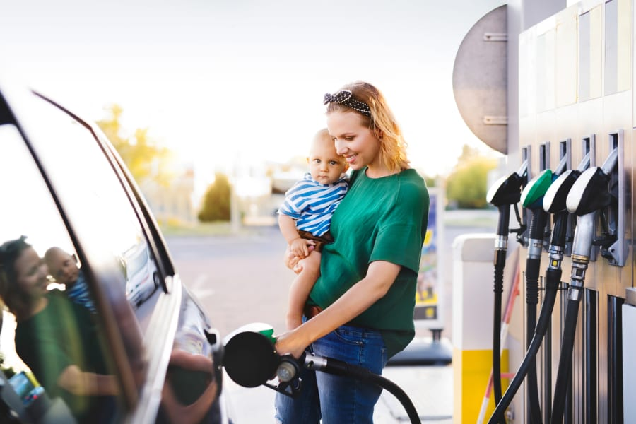 A mom fills her car up with gas