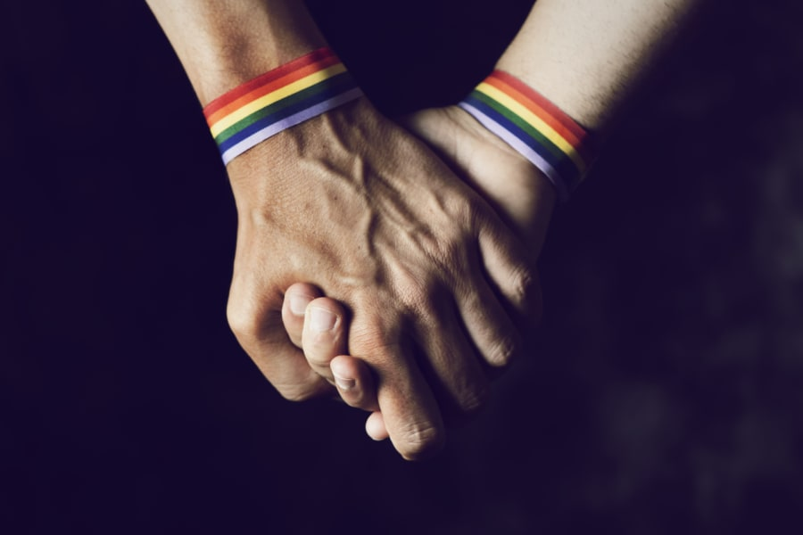Two people hold hands while wearing LBGTQ flag wristbands