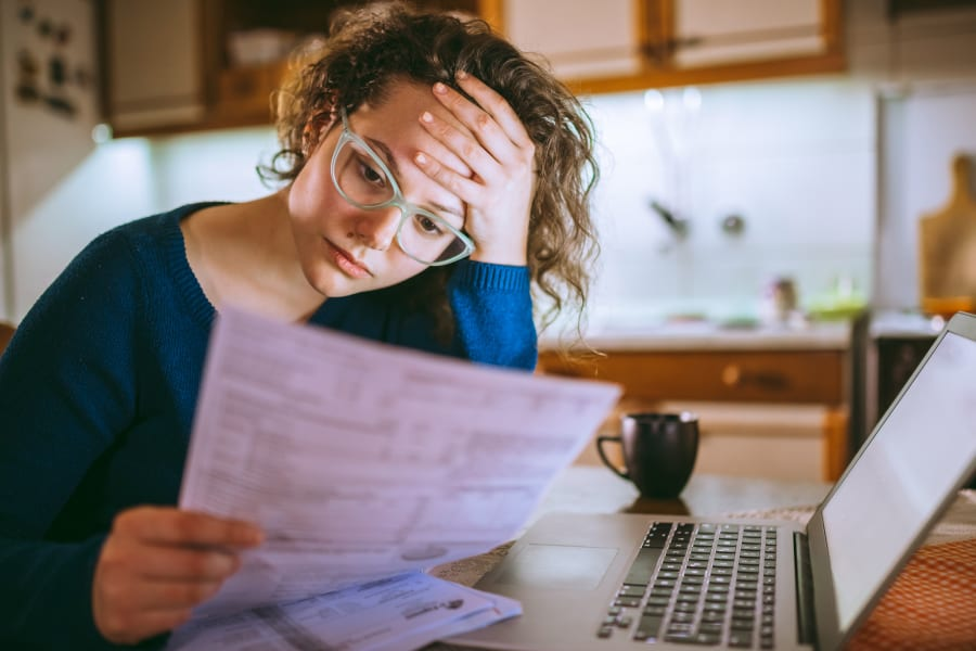 A stressed young woman looks over bills