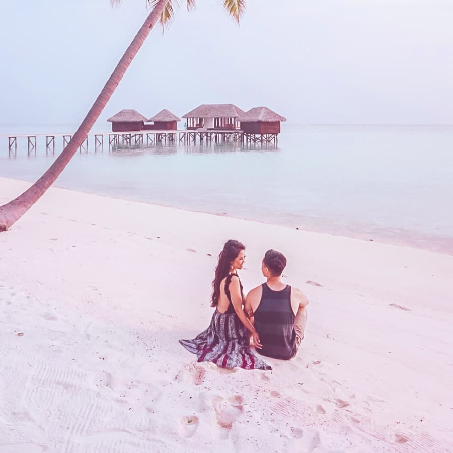 The couple sits on the beach and enjoy the resort.