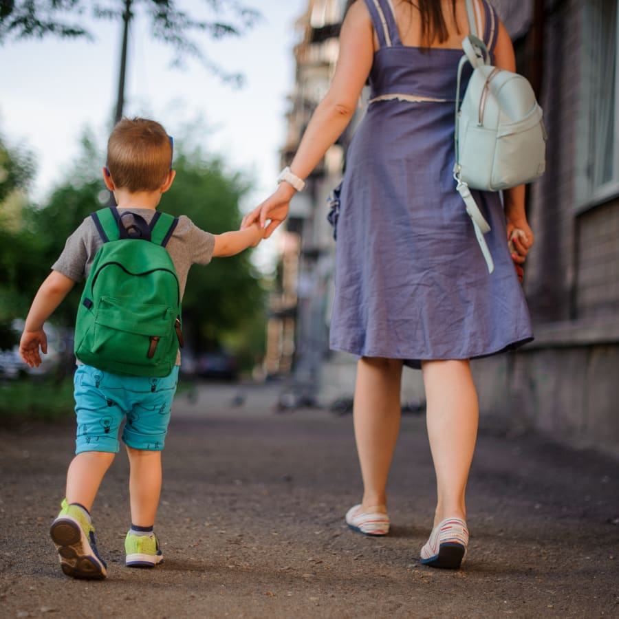 A mother and young son walk holding hands