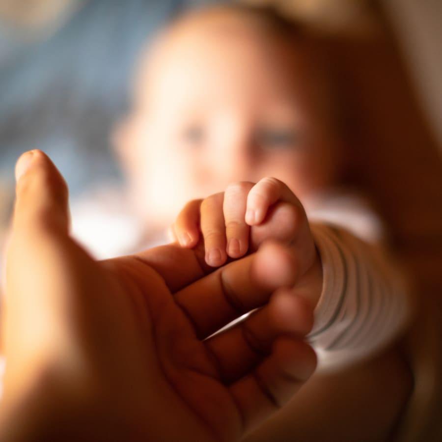 A newborn grasping their parent's finger