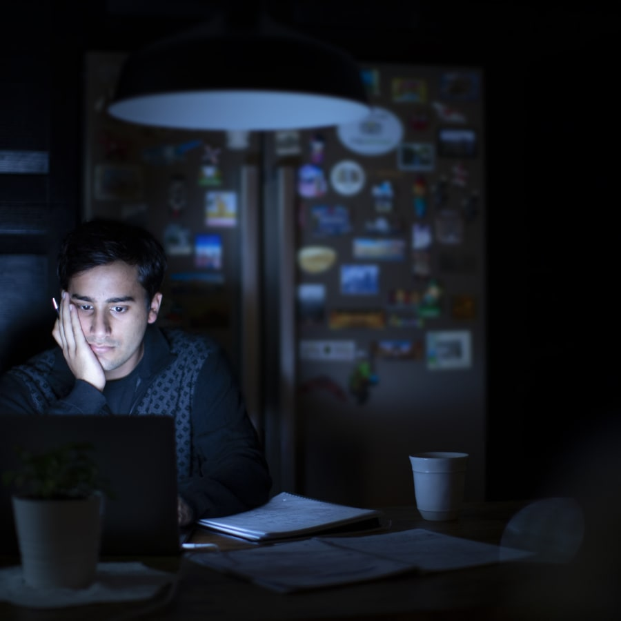 A student studying in their kitchen late at night