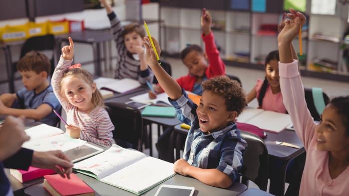 Children raise their hands in a classroom.