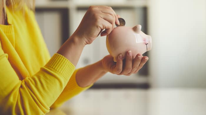 A woman puts a coin into a piggy bank