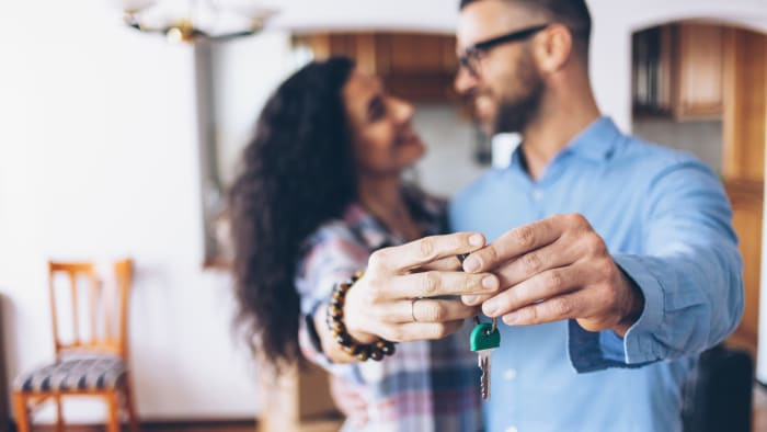 A young couple holds the keys to their new home
