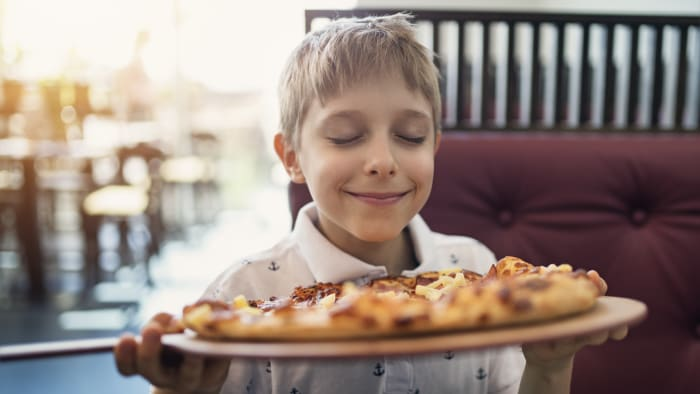 A kid and his pizza