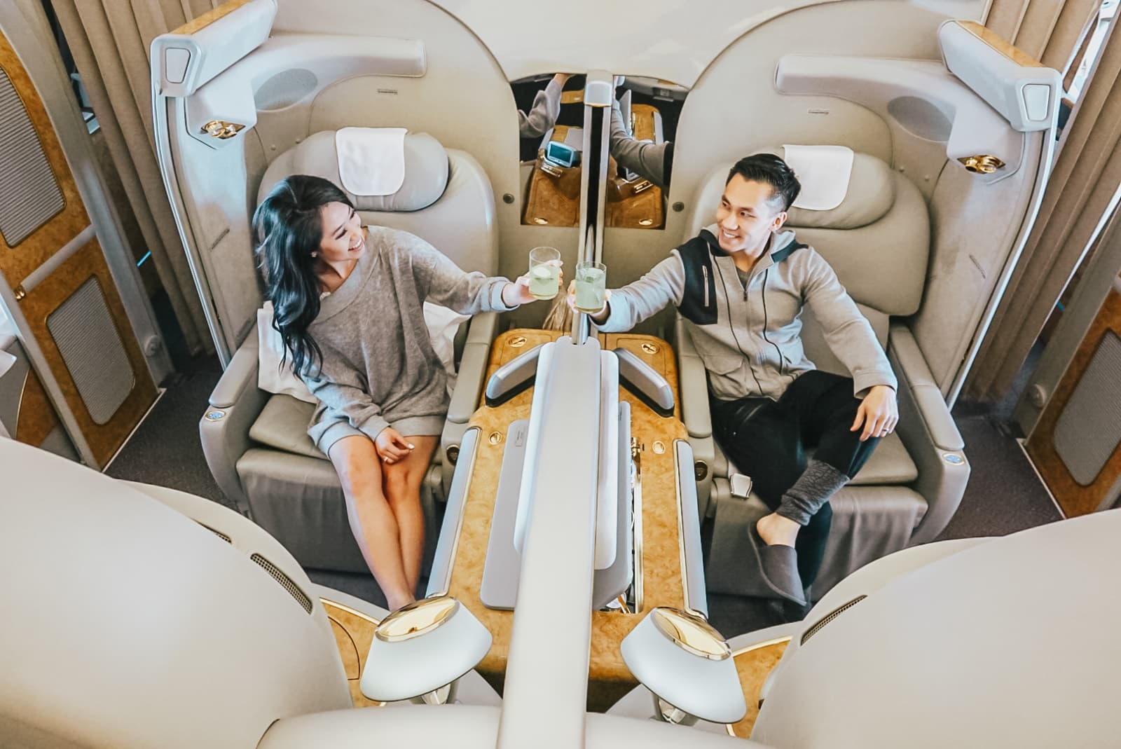 The two toast each other while sitting in first-class.
