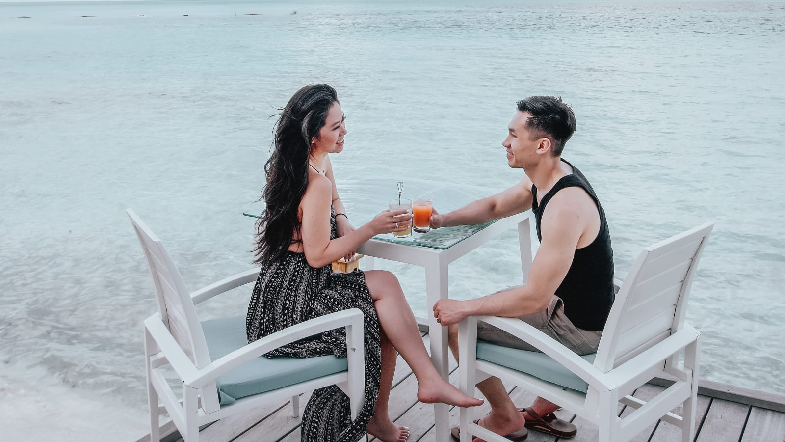 The couple sits at a table each with a drink in their hand.