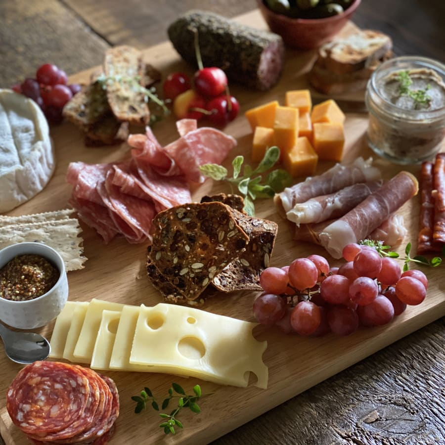 a charcuterie board with meats, cheeses, and fruits