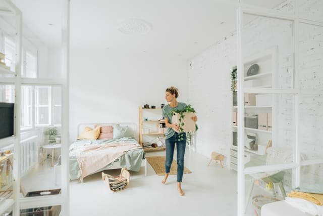 person moving around plant in a bedroom
