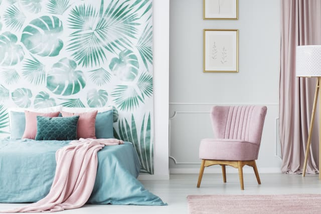 This room shows vibrant wallpaper that adds a pop of drama to the pastel bedroom